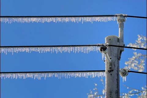 Icicles on row of powerlines after ice storm, against blue sky